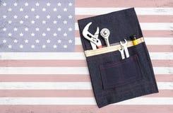 Les outils en acier dans la conception empochent le sac d'outillage sur le fond abstrait de drapeau des Etats-Unis Photos libres de droits