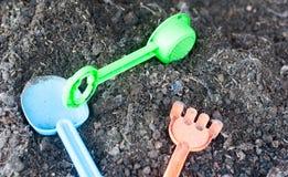 Les outils en plastique d'agriculture comme la herse et la pelle ont mis dans le sol noir prêt à utilisé pour l'étude d'enfant photographie stock libre de droits