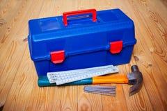 Les outils enferment dans une boîte, martèlent, les clous et la règle de pliage sur le fond en bois photo stock