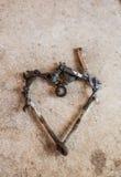 Les outils et les pièces ont arrangé à un coeur d'amour sur le ciment Images stock
