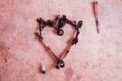 Les outils et les pièces ont arrangé à un coeur d'amour sur le ciment Photographie stock