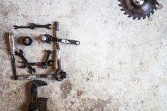Les outils et les pièces ont arrangé sous forme de visage souriant sur le ciment Photographie stock