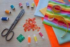 Les outils pour coudre pour le passe-temps ont placé sur la vue supérieure de fond en bois de table Fil, aiguilles et tissu Photo libre de droits