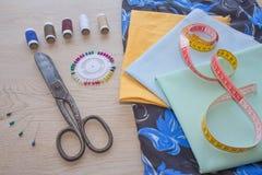Les outils pour coudre pour le passe-temps ont placé sur la vue supérieure de fond en bois de table Fil, aiguilles et tissu Photos libres de droits