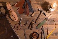 Les outils pour faire des chaussures se trouvent sur une table en bois Ensemble d'articles symbolisant le travail manuel, petite  image stock