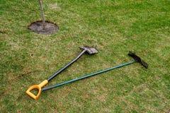 Les outils sales du jardinier se trouvent sur la pelouse roulée fraîche images stock