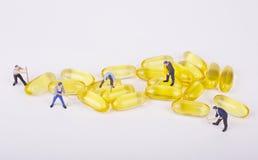 Les ouvrières miniatures de personnes signalent avec la médecine Images libres de droits