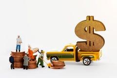 Les ouvrières miniatures de personnes sur l'argent inventent des piles avec le camion pick-up sur le fond brouillé photographie stock libre de droits