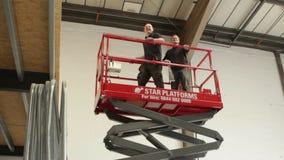 Les ouvriers actionnent la plate-forme de levage dans le chantier de construction banque de vidéos