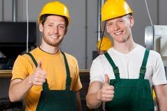 Les ouvriers de fabrication montrant des pouces lèvent le signe photographie stock