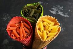 Les pâtes colorées crues en gros plan en gaufre ont coloré le cône Le concept de couleur et de la nourriture Vue d'en haut, confi photographie stock