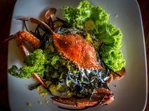 Les pâtes d'encre de calmar avec un crabe entier ont servi dans un plat image libre de droits