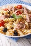Les pâtes de Fusilli avec le thon, le parmesan et les tomates dans une cuvette clôturent u Photo stock
