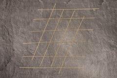 Les pâtes de spaghetti sur la surface de fonctionnement grise ont assuré l'orteil de pointe de coutil Photo stock