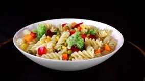 Les pâtes en spirale avec des légumes d'un plat tournent sur un fond noir Le chou-fleur vert tombe d'un plat banque de vidéos