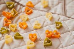 Les pâtes italiennes colorées différentes aux coeurs forment sur les textiles de cuisine Fond de nourriture Macaronis colorés en  Images stock
