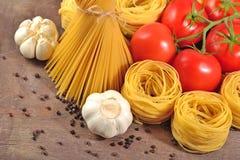 Les pâtes italiennes crues, les tomates mûres s'embranchent, ail et p noir Photo stock