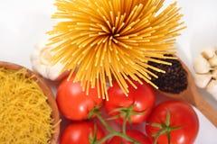 Les pâtes italiennes crues, les tomates mûres s'embranchent et poivre noir dessus Images libres de droits