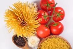 Les pâtes italiennes crues, les tomates mûres s'embranchent et poivre noir dessus Image stock