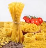 Les pâtes italiennes crues, les tomates mûres s'embranchent et poivre noir dessus Photo libre de droits