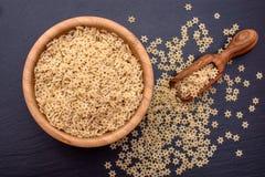 Les pâtes sous forme de starlettes se situent dans une tasse en bois et un scoop en bois sur un conseil en pierre noir, l'espace  Images libres de droits