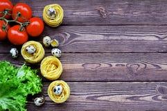 Les pâtes, tomates, oeufs se trouvent sur une table en bois Images libres de droits