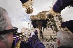 Les pénitents touchent de grandes trompettes à Virgen de los Dolores dans un cortège de semaine sainte Photographie stock