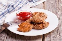 Les pépites de poulet avec le tomate sauce sur le conseil en bois Images stock