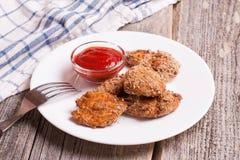 Les pépites de poulet avec le tomate sauce sur le conseil en bois Images libres de droits