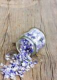 Les pétales bleu-clair de fleur ont plu vers le bas des pots en verre Photos libres de droits