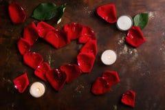 Les pétales de rose rouges au coeur forment avec les bougies blanches sur le brun foncé et le fond d'or Aimez, romance, anniversa photo stock