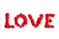 Les pétales de rose rouges ont placé dans le mot l'AMOUR, concept de jour du ` s de valentine Photos libres de droits