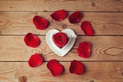 Les pétales et le coeur de fleur de Rose forment la tasse de café sur la table en bois Photos libres de droits