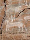 Les pétroglyphes le cavalier antique avec le drapeau Photographie stock