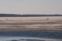 Les pêcheurs de paysage d'hiver sur la rivière glacent la pêche une journée de printemps Image stock