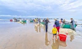 Les pêcheurs font les filets de pêche sinistres de travail Image stock