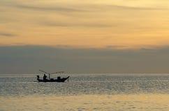 Les pêcheurs pêchant sur une silhouette de bateau dans le lever de soleil de matin s'allument Images stock