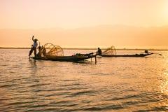 Les pêcheurs pêche des poissons pour la nourriture dans le lever de soleil dans le lac Inle photographie stock