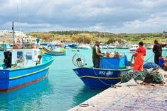 Les pêcheurs sur Luzzu ont coloré le bateau au port Malte de Marsaxlokk Photographie stock
