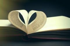 Les pages d'un livre ont courbé dans une forme de coeur images libres de droits
