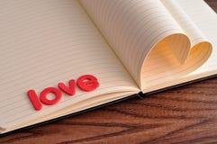 Les pages d'un livre se plient dans une forme de coeur montrée avec l'amour de mot Image libre de droits