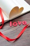 Les pages d'un livre se plient dans une forme de coeur montrée avec un ruban rouge et l'amour de mot Photo libre de droits