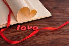 Les pages d'un livre se plient dans une forme de coeur montrée avec un ruban rouge et l'amour de mot Photos stock
