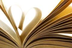 Les pages d'un livre se sont pliées dedans à une forme de coeur Photographie stock