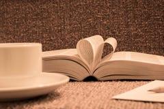 Les pages du livre ouvert ont roulé dans la forme de coeur avec du café sur la table Image stock