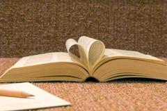 Les pages du livre ouvert ont roulé dans la forme de coeur sur la table Images libres de droits