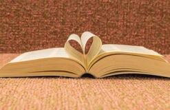 Les pages du livre ouvert ont roulé dans la forme de coeur sur la table Photos stock