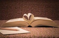 Les pages du livre ouvert ont roulé dans la forme de coeur sur la table Photographie stock