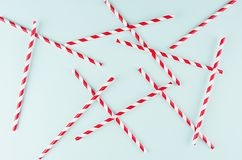 Les pailles rayées rouges de cocktail sur le pastel monnayent la couleur en tant que fond joyeux abstrait, modèle aléatoire image stock