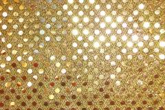 Les paillettes d'or sur le tissu métallique façonnent le fond/modèle image stock
